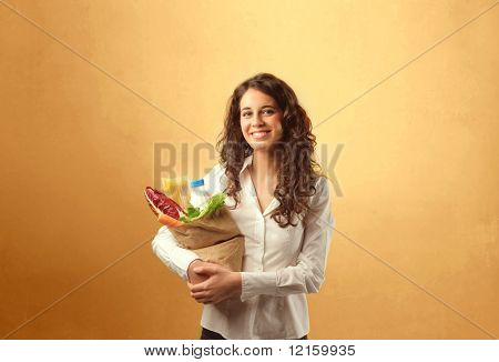Smiling woman carrying a bag with vegetables in it