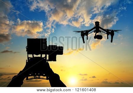 Man hands handling drone against sunset silhouettes poster