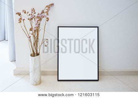 Mock up black photo frame on floor Home interior decoration with flower