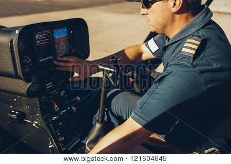 Helicopter Pilot Checking The Gauges