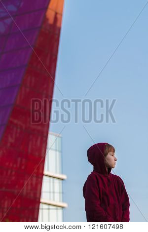Street portrait of teenage boy wearing dark red hooded sweatshirt  at glass high-rise building backg