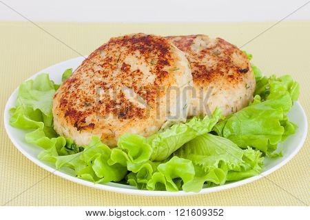 fish cutlet on a plate with fresh green salad lettuce pollock cod white fish hake