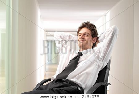 Businessman relaxing on a chair in an office