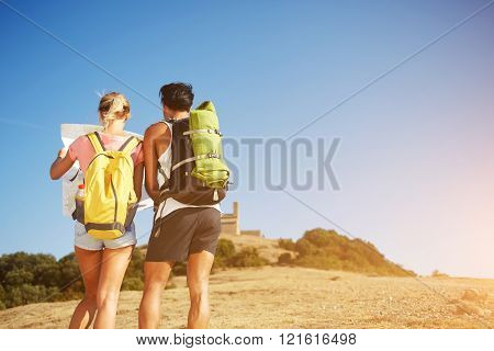 Back view of a man and woman travelers are searching way on a location map during their hiking in sunny day two young wanderers are taking break between walking in mountains during summer vacation