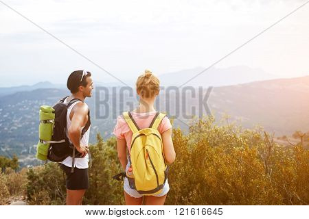 Back view of a young couple are enjoying beautiful landscape while standing on a high mountain in day man and woman wanderers are resting after hiking during their summer travel in new countries