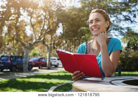 Young attractive woman is smiling for someone while is sitting with notepad in park in summer day happy cheerful female is enjoying book and recreation time during her long awaiting spring weekend
