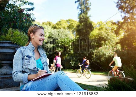 Young cheerful female is looking on something funny while is sitting with her diary in park in warm spring day happy smiling woman is enjoying leisure and rest during long awaiting weekend overseas