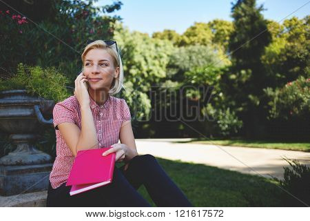 Hipster girl with good mood is calling via cell telephone while sitting in the fresh air in warm spring day gorgeous female is talking with her friend via mobile phone while resting in park outdoors