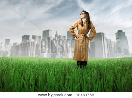 Woman wearing a raincoat standing on a green meadow with cityscape on the background