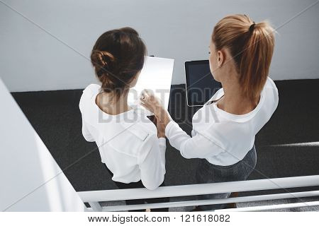Top view of woman boss is holding digital tablet and looking at paper documents that keeping her secretary. Two female business partner are using touch pad for verification of information from reports