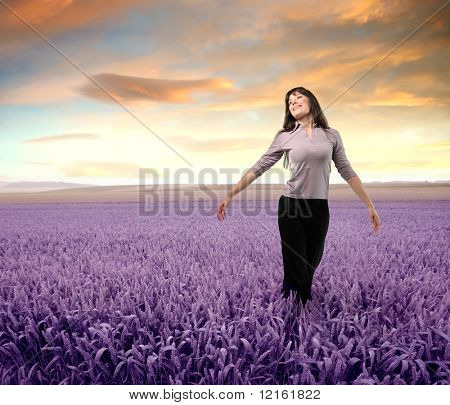 Woman standing with open arms on a lavender field