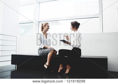 Smiling woman manager listening funny story from colleague that sitting near with portable touch pad in hand. Female entrepreneur is holding digital tablet and telling partner about successful meeting