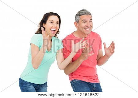 Excited couple cheering on white background