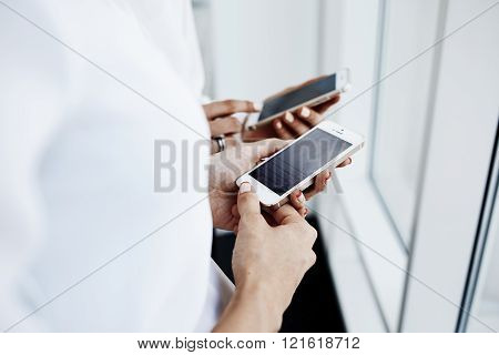 Two business female are reading finance news on mobile phone during work break