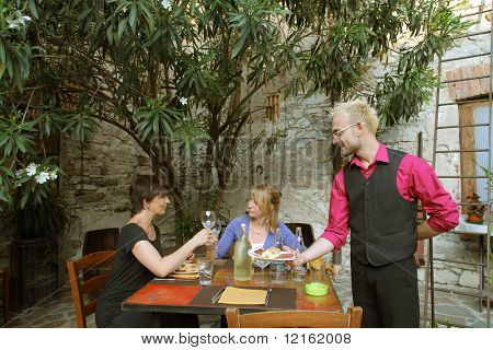 Young waiter serving a dish to two women