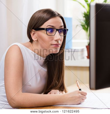 Surprised Businesswoman Reading From Monitor