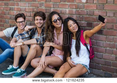 Hip friends sitting on the floor and taking selfie against bricks wall