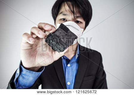 Young business Asian guy wearing protect air mask, looking at coal, selective focus on coal