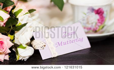 Mothers day deutch congratulation card and roses on wooden board