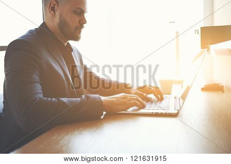 Male economist is analyzing the activities of the company via net-book