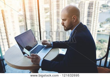 Male serious CEO is using cell telephone during work on net-book