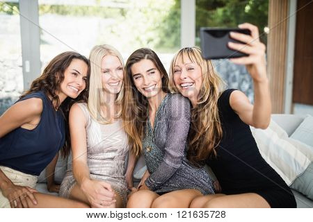 Beautiful women smiling and taking selfie with mobile phone at party