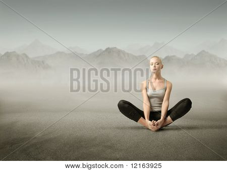 Beautiful woman meditating on a mountain