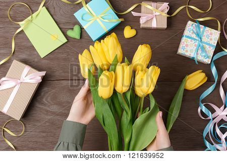 Female hands with tulips and gift box on wood