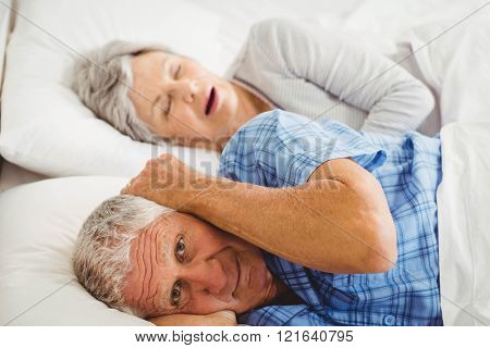 Senior man covering her ears while man snoring in bed