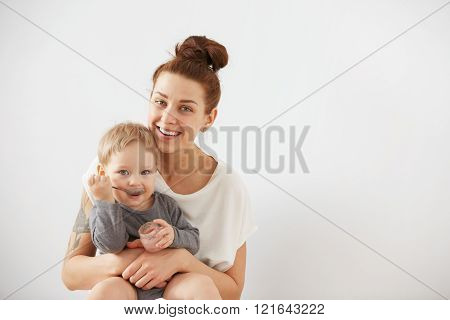 Young Attractive Mother With Her One Years Old Little Son Dressed In Pajamas.  Boy Eating A Fruit Sm