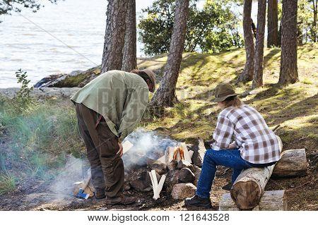 Senior Couple Tending Camp Fire