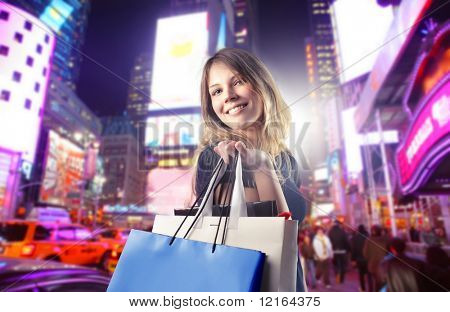 Smiling woman carrying some shopping bags on a city street