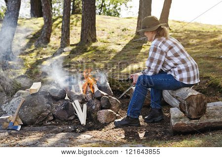 Senior Woman Lighting Camp Fire