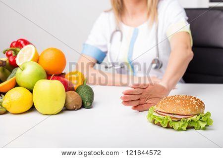 Health professional pushing away burger