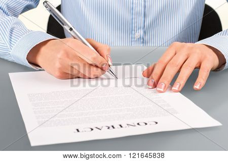 Female signing contract at desk.