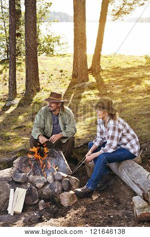 Senior couple sitting by camp fire