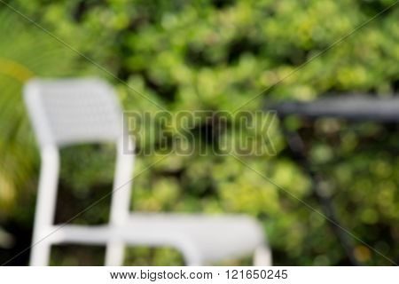 Blurred Defocussed abstract background of green garden with white chair and table with bokeh