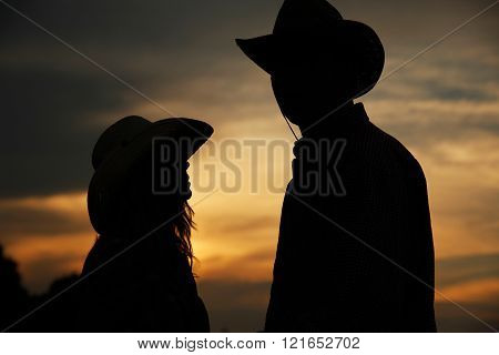 Young Couple In Love On Haystacks In Cowboy Hats