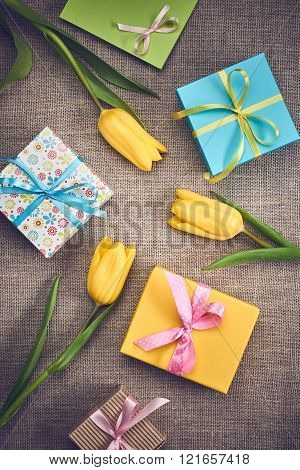 Mothers Day background. Tulips, gifts on sackcloth
