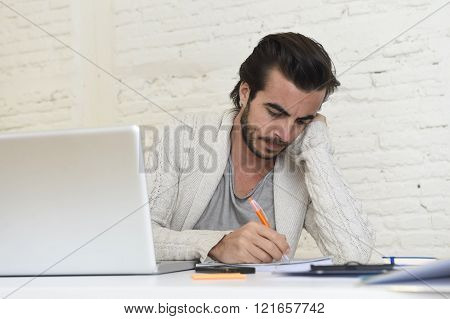 young attractive student preparing university project writing on pad with pen or hipster style freelancer businessman working with laptop computer analyzing project at home office studio