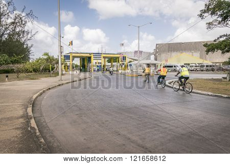 BRIDGETOWN, BARBADOS, 21 DECEMBER 2015 - workers cycling to work  at Bridgetown Port with view of port entrance