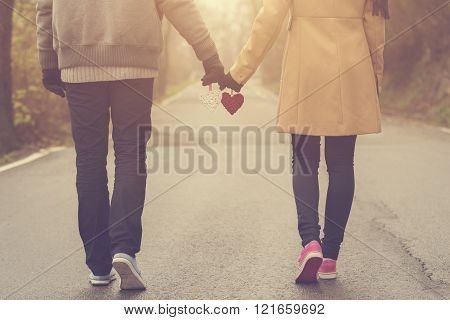 Couple in love holding hearts on the road.