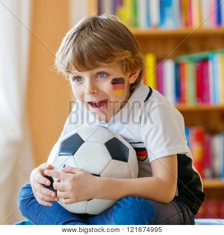 Kid boy watching soccer or football game on tv