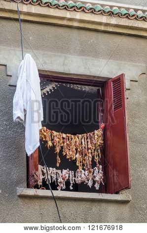 Guts of sheep hanging on rope and exposed in window to sun and wind