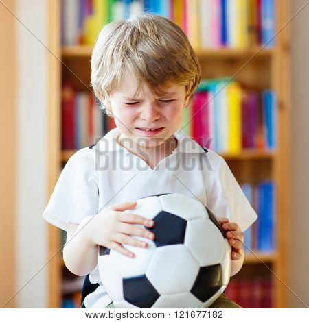 Kid boy sad about lost football or soccer game