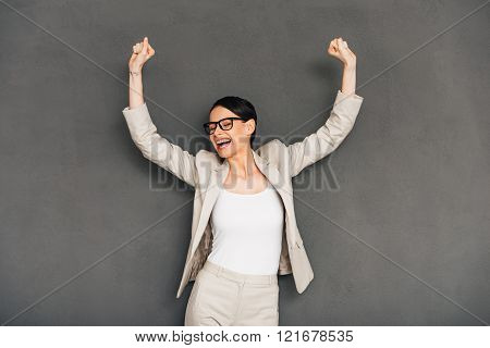 Hurray! Cheerful young businesswoman in glasses gesturing and keeping her mouth open while standing against grey background