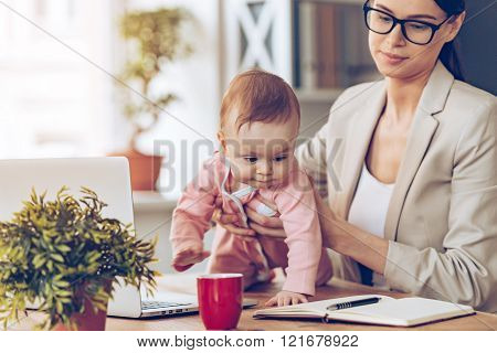 Let me examine your working place! Little baby girl looking away while crawling on her mothers place of work