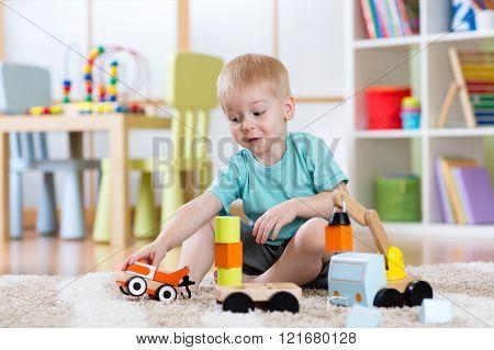 kid boy toddler playing car toys at home