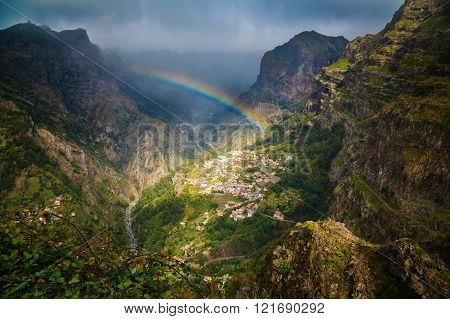 rainbow above mountain village
