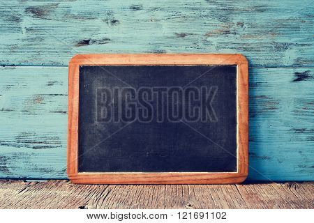 a blank old wooden-framed blackboard on a rustic wooden surface, against a blue rustic wooden background